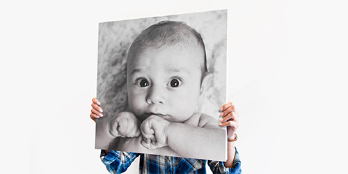 Three different canvas print sizes of a smiling baby with mom and dad. Pinned on a wall above a desk with plants
