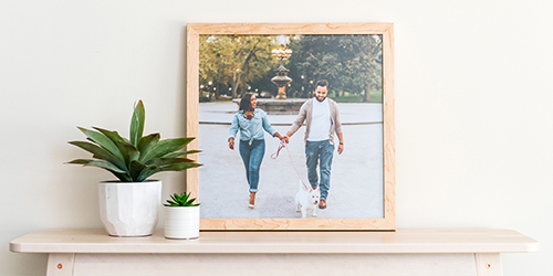 Framed pic of Newlywed couple next to a black and white framed photo print on a desk with two flower pots