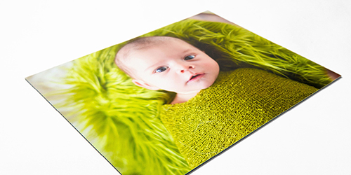Baby wrapped in a green blanket with a green background on a Styrene photo print