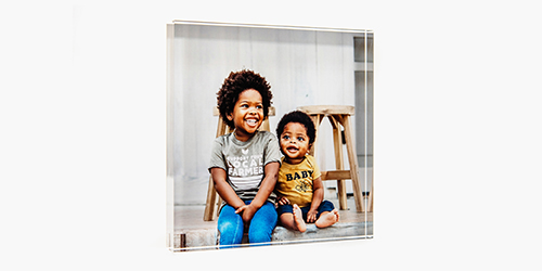 siblings siting and smiling on a acrylic wall decor hanging on a wall