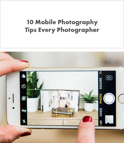 taking a picture of a desk with plants and custom photo book on a cellphone