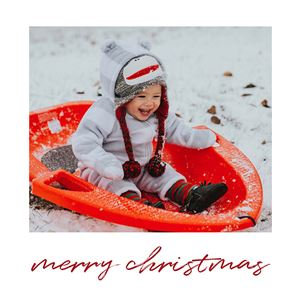 Baby on a sled in the snow on the cover of Christmas Themed Buzz Book
