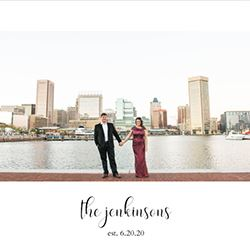 engaged couple hold hands and stands infront of the Inner Harbor in Balt=imore, Maryland