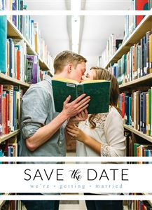 Couple kissing in the library while holding a book on a Custom Save The Date Photo Card