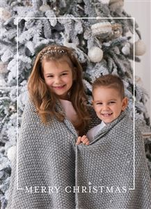Sibling smiling in front of a snowy pine tree on a Custom Christmas Card