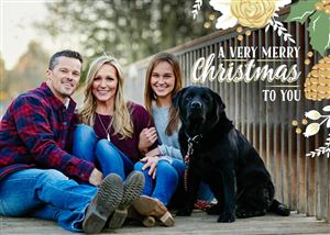 Family of three pose with their black lab on a bridge on their Custom Christmas Card
